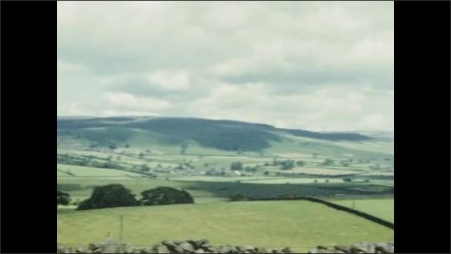 1950s: EUROPE: view across Yorkshire Moors. Clouds over landscape. Dry stone wall. Car by road side.