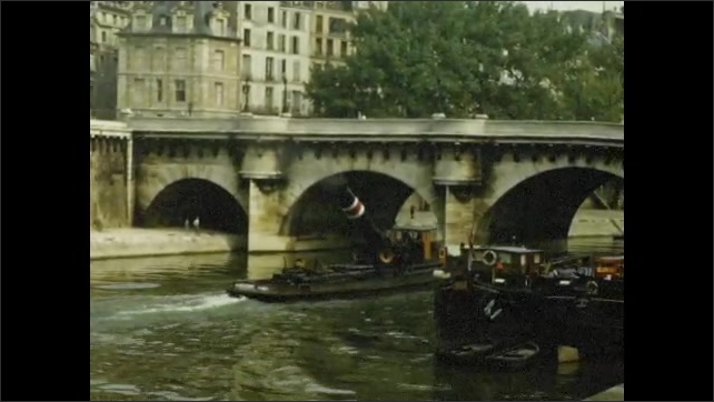 1950s: Boat on river, boat passes under bridge.