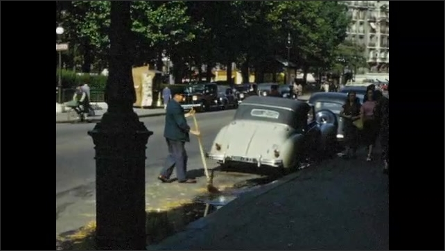 1950s: Horse and carriage parked on street. Man sweeping street, people on sidewalk.