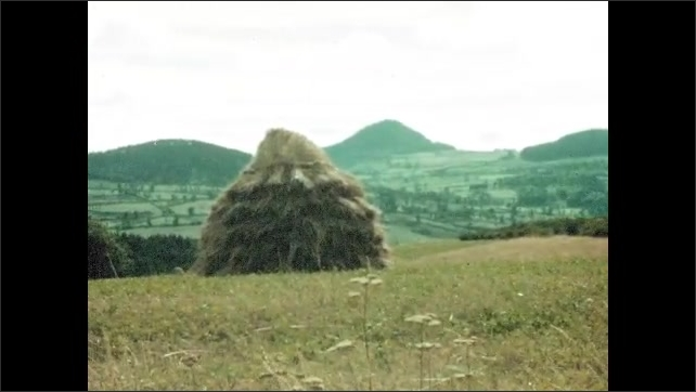 1950s: Intertitle. Pan across mountains, field. Pan across mountains, haystack in field. Building on hill, pan to house.