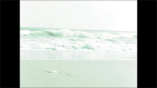 1950s: Boy playing in sand on beach. View of waves. Footsteps in sand. Intertitle.