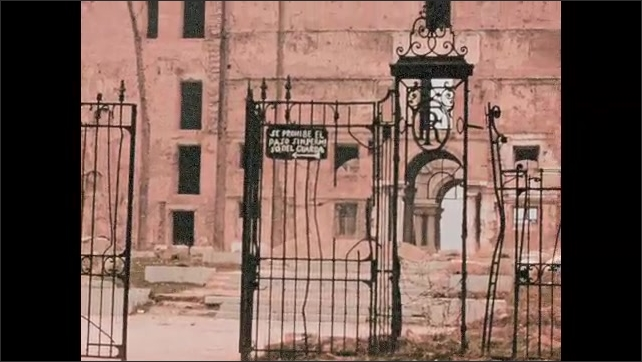 1950s: EUROPE: SPAIN: university building in Madrid. Gates of university. Old stone building. Spikes on railings. Statue of horse