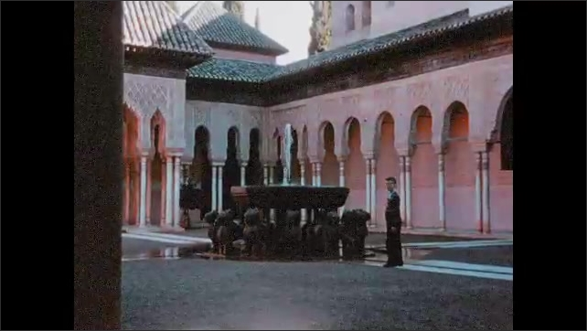1950s: Spanish city. Pink building. Boy stands in courtyard of pink building. Water fountain in courtyard.
