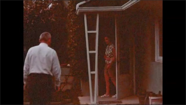 1960s: People pack things in trunk of car. Men and women exit house, hug.