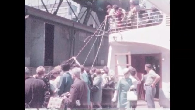 1960s: People stand on dock. Streamers stream from ship to dock. People wave.