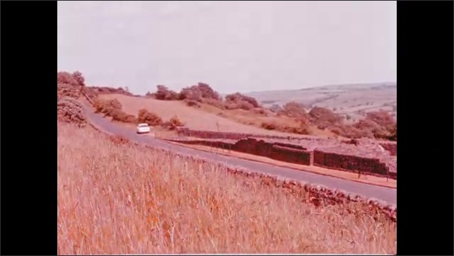 1960s: Empress of Canada ocean liner at dock. Car on road in rural area. Women stand by stone wall.