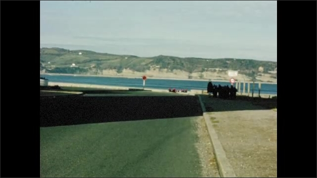 1960s: Two adults accompany group of children down road towards beach.