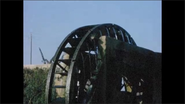 1960s:  EUROPE: water wheel by river. Water wheel turns. Man with horse and cart. Chickens and cat on farm