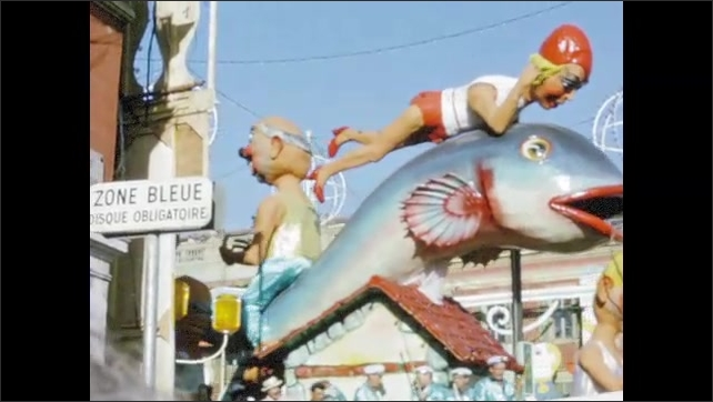 1960s:  EUROPE: lady rides fish in carnival parade. Large heads in parade.