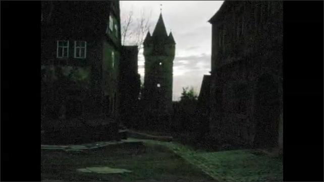 1960s: City.  Dog sniffs fence and walks along road.  Castle.  Sky.