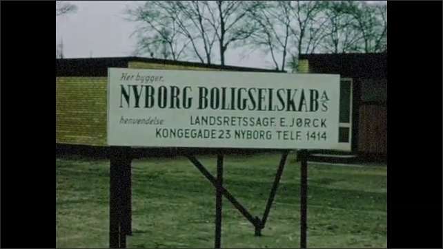 """1960s: Village street.  People walk along.  Building.  Sign reads """"NYBORG BOLIGSELSKAB.""""  City.  Traffic.  Horses pull carriage."""