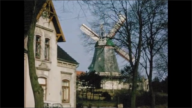 1960s: Body of water in city. Windmill with blades turning.