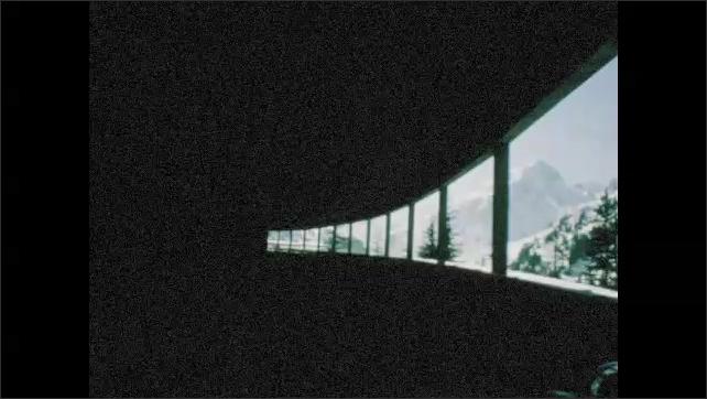 1960s: Car drives through snowy town. Car drives through tunnel.