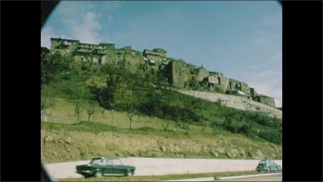 1960s: Cars and bicyclists travel down street. Ruins on mountainside. Cars drive along highway. Woman poses by car on side of the road.