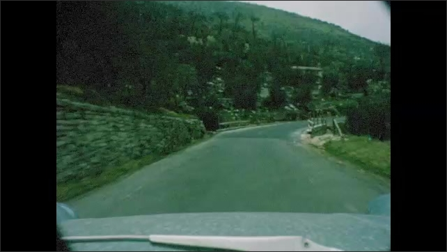 1960s: Car drives through rural area. Cows pulls carts.