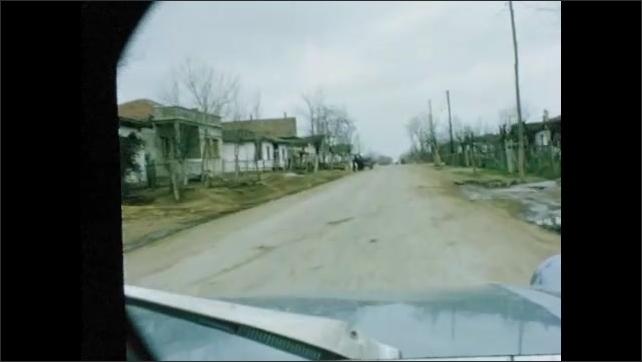 1960s: Animals in field. Car drives through rural town.