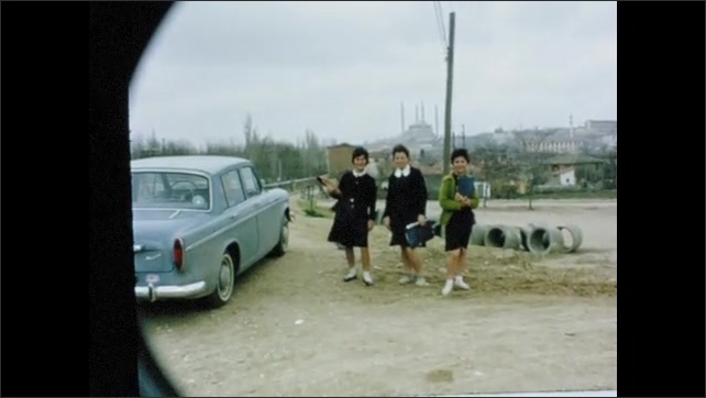 1960s: Car drives through rural town. Women pose next to car. Clouds and sky.