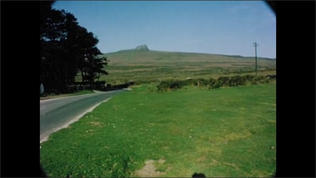 1960s: EUROPE: sheep eat grass by road. Tor on top of hill. White sheep with horns. Country house