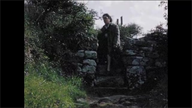 1960s:  EUROPE: ENGLAND: lady looks at flowers. Lady stops for rest on walk. Lady climbs over stile. Visit to Chysauster.