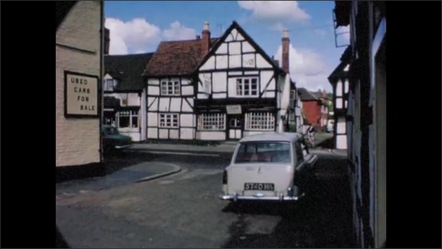 1960s:  EUROPE: ENGLAND: cars drive through village. Buildings and cottages in village. Tudor buildings