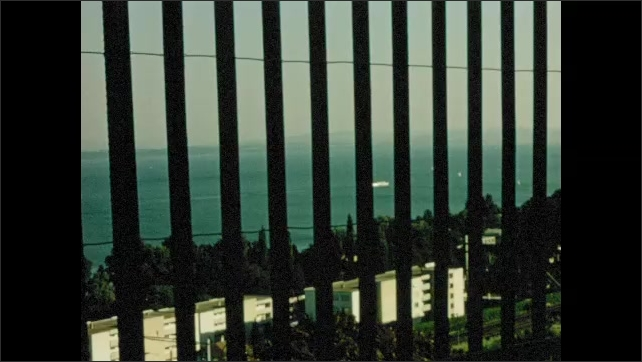 1970s: EUROPE: SWITZERLAND: NEUCHATEL: view of coast through railings. Danger of death sign. People wait in line