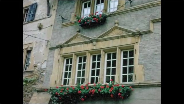 1970s: EUROPE: SWITZERLAND: NEUCHATEL: shop in town square. View along street in village. Decoration on windows of building.