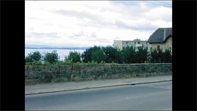 1970s: EUROPE: SWITZERLAND: NEUCHATEL: water in fountain and trough in village square. Sign for Neuchatel. Bread shop in village. Lady waves from balcony