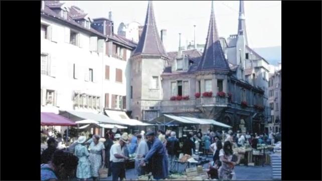 1970s: EUROPE: SWITZERLAND: NEUCHATEL: town market in street. Visitors to market. Lady sells veg.
