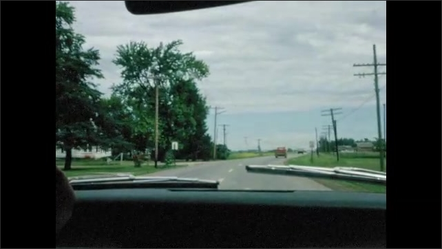1960s: UNITED STATES: plane in sky. Planes on runway. View of road through car window. Clouds over road.