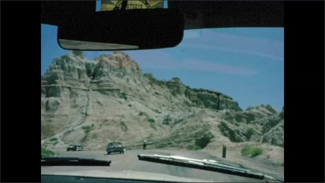 1960s: UNITED STATES: drive towards mountains. Rocky landscape. Drive to Yellowstone National Park. Interior mirror in car. Mt. Rushmore Memorial sign. Faces in rocks.