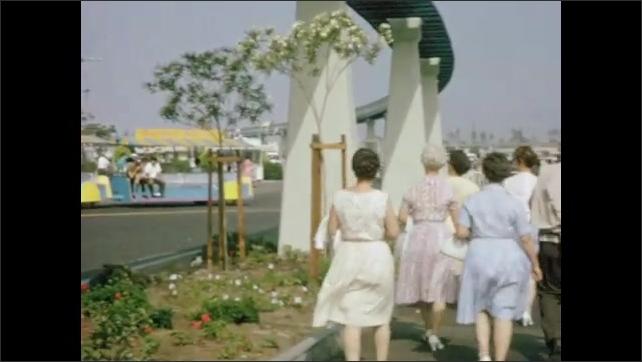 1960s: Cars and people walk past Grauman's Chinese Theater. Men and women walk beneath monorail and past mascot. Mascot shakes children's hands at Disneyland.
