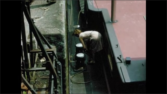 1960s: Barge in canal.  Woman hands ropes to men on shore.  Man turns crank.