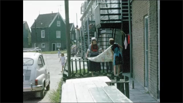 1960s: UNITED STATES: boat on canal. Ladies shake out laundry. Boy on bike by canal.