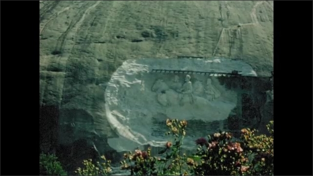 1970s: MEXICO: lady observes rock carving in cliff. Carved stone cliff. Street sign