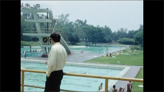 1970s: MEXICO: bulls in pen. Statues of bulls. Man looks over rail. Outdoor swimming pool.