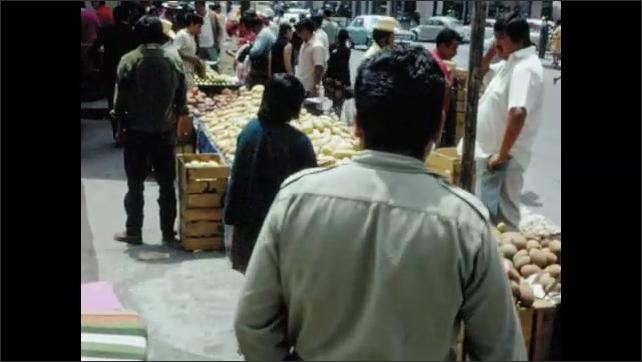 1970s: MEXICO: ladies walk along road. Visit to street market and stalls. Fruit at market. Girl pulls face at camera.