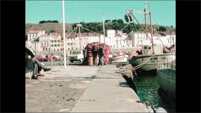 """1970s: Car drives around curve in road, cliffs, low stone wall. Sailboats tied up in harbor bob gently, scrubby hill, seaside village, men stand, sit on bench. """"Gendarmerie Nationale"""" boat."""