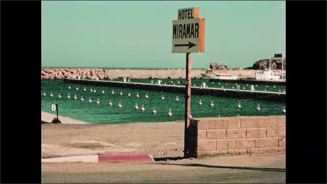 "1970s: Harbor, rock sea wall, buoys, dock, sign: ""Hotel Miramar."" Buildings on steep cliffs, family sits on wall."