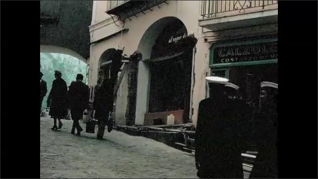 1970s: Mediterranean, steep village street, shops, man on ladder hammers building, sailors walk past. Clock tower. Pergola by water.