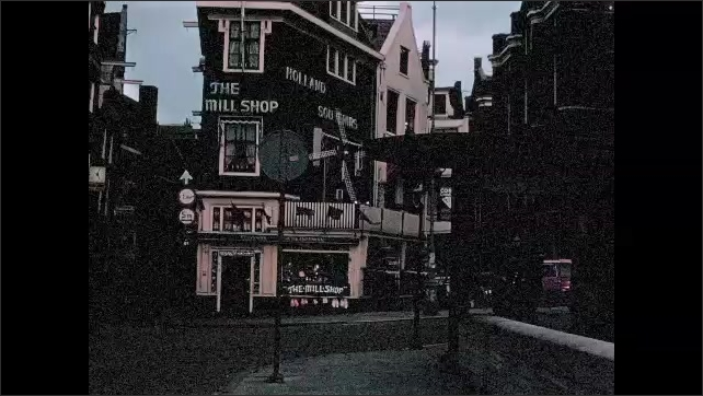 1970s: AMSTERDAM: street in Amsterdam. Pedestrians in street. Shop signs. Mill turns on building. Boats on canal.
