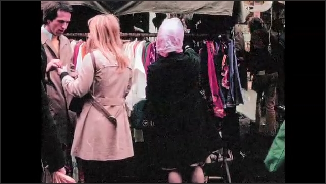 1970s: ENGLAND: ladies shopping for clothes at Portobello Road market. Lady with Indian clothes.