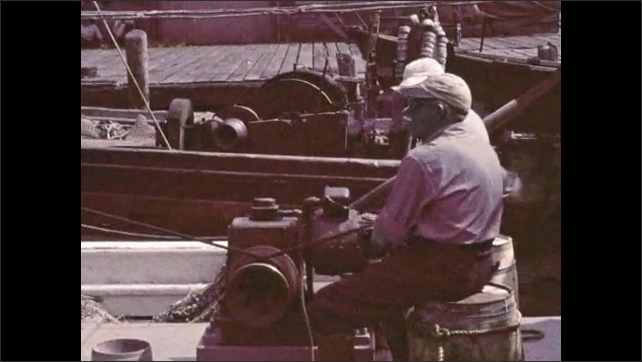 1950s: Man dumps basket of caught fish onto conveyor belt on docks. Men unload fishing boat with crane. Caught fish ride up conveyor belt.