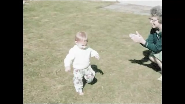 1970s: Child sits in grass yard then stands up and walks around. Child throws inflated box on ground in yard then picks it up and plays with it.