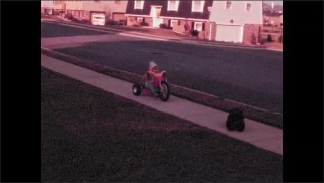 1970s: Children scoot around driveway on toy vehicles. Man stands on sidewalk with dog.