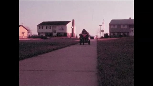 1970s: Children play in front yard. Child rides tricycle down sidewalk. Man puts object into trunk of car. Woman gets into passenger side of car.