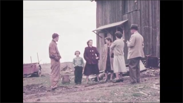 1950s: Man and woman sit on couch, woman reads paper. Boy sits on floor, plays. People stand outside barn, talk.