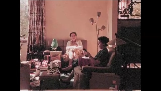 1950s: Family sits together and opens Christmas presents.