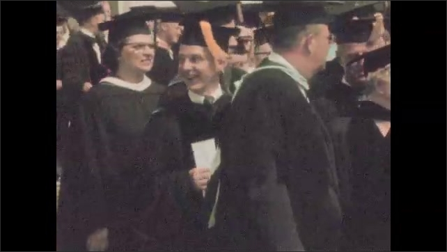 1950s: Student walks off stage. Graduates get on bus. Graduates stand around outside.