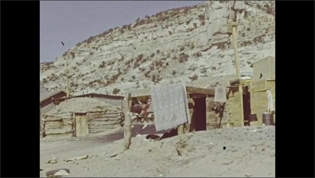 1940s: Small wooden cabin. Small village. Old woman sits with small children.