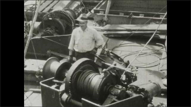 1930s: Man catches suitcase dropped down chute. Man stands next to cable spool. Men on deck of vessel.